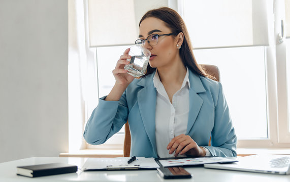 Pretty young woman in the office drinking water while working. Drinking from glass.