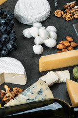 different varieties of cheese with fruits, nuts, dried fruits and kitchen utensils for cheese plate. Roquefort, Maasdam, emental, Gouda, Parmesan, mozzarella and other cheeses
