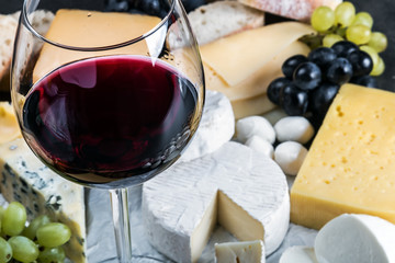 glass of red wine on the background of assorted cheeses, soft, hard, rennet and brine with fruits, nuts