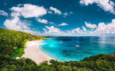 Grand Anse beach at La Digue island in Seychelles aerial panoramic view. White sandy beach with blue ocean lagoon and catamaran yacht moored