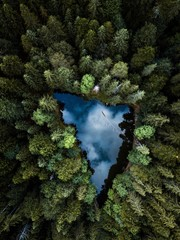 Aerial view of small blue alpine lake in the green pine forest near the Eibsee lake,Germany,Europe.