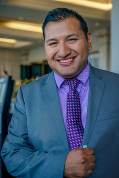 A young thirty year old latino gentleman dressed in a grey business suit and complimentary violet tie and shirt while smiling and standing outside a building.