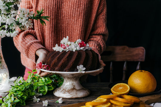 Homemade bundt cake with flowers on a wooden table.