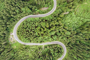 Poster de jardin Route dans la forêt Top down aerial view of winding forest road in green mountain spruce woods.