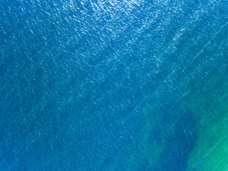 Blue water background and sun reflections. Water textured surfac