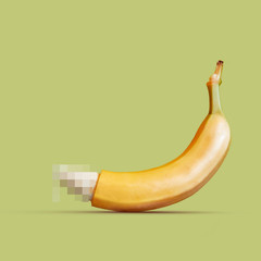 Large banana as a symbol of the penis on a yellow background.