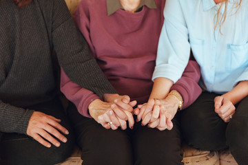 Three generations of women hold hands.