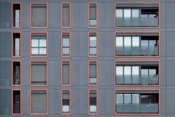 Orange framed windows in gray wall