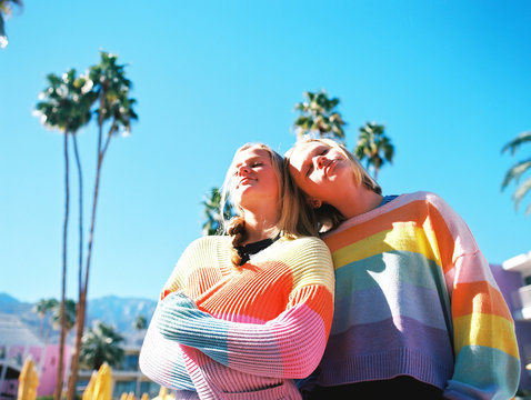 Teenage girls in rainbow striped sweaters standing outdoors