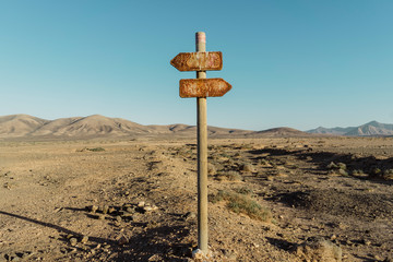 Old road sign between desert and blue sky