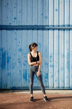 Young runner in front of a big blue metal door