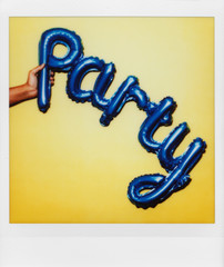 polaroid of a balloon in the shape of the word party