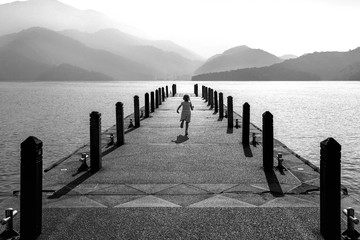 Wall Mural - Black and white of Little girl running on pathway in Sun moon lake, Taiwan.