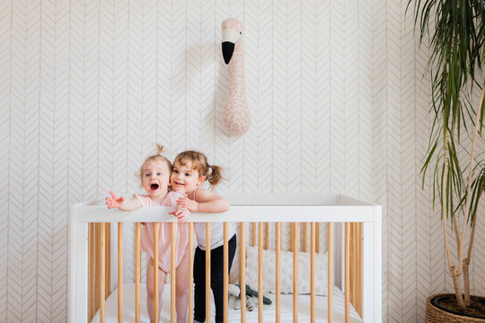 Sisters playing in a crib together