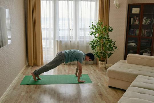 Man training yoga at home