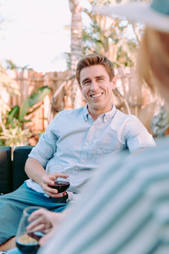 Young man smiling while having a glass on wine with his lover.
