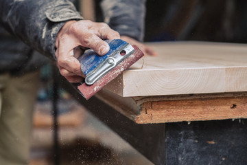 Carpenter sanding plank