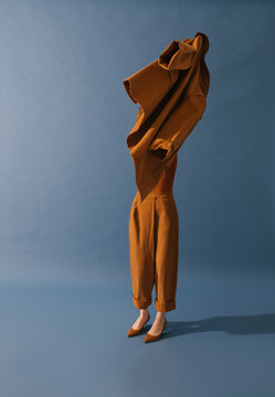 model with brown outfit on blue background