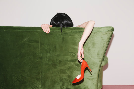woman with pink pleated skirt on green velvet couch