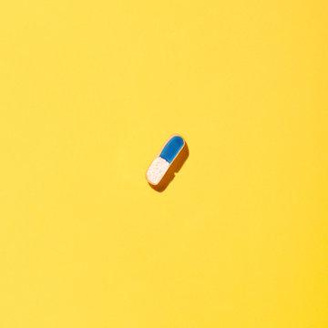 Pills on yellow background.
