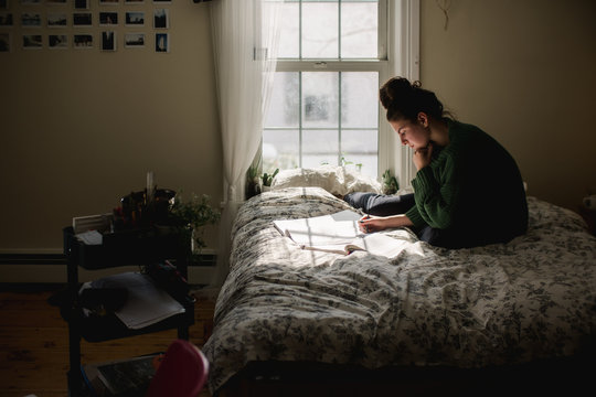 teen studying on her bed