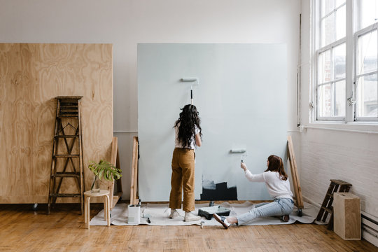 two women painting a backdrop in a modern bright industrial studio space