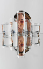 Portrait of woman wearing sunglasses distorted through glasses with water