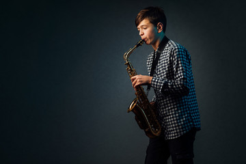 A boy on a dark background with a searchlight plays saxophone Fotobehang