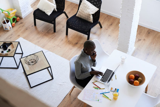 Black afro woman working from home in messy table.