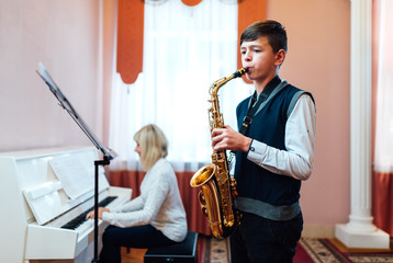 A teenage boy learns to play saxophone in a music lesson to accompaniment of a female teacher on the piano. Fotobehang