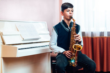 student boy plays saxophone while sitting at a music lesson in class Fotobehang
