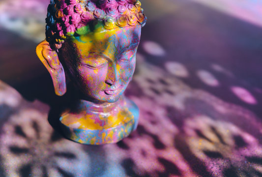 Colorful, vibrant Buddha figurine painted in bright, rich colors
