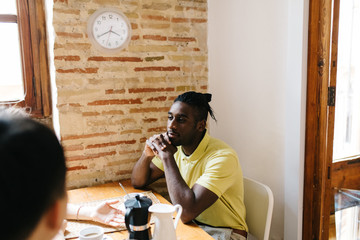 African American man sitting at table with hot drinks with frien
