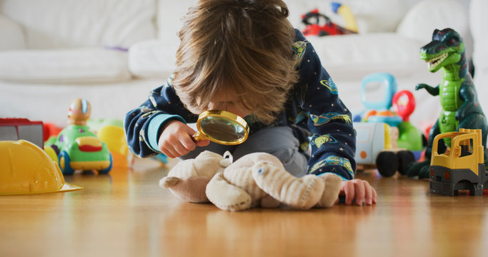Cute little boy using magnifying glass