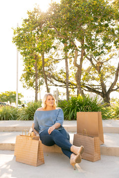A young blonde woman sits on a bench at an outdoor mall surrounded by shopping bags.