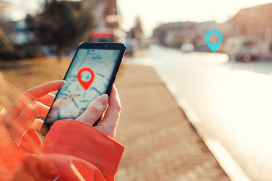 Concept of Internet maps and navigation. Female hands hold smartphone with maps app, and marked location icon, red and blue destination icon