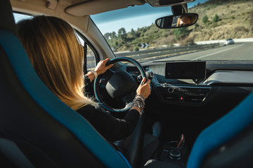 Blonde woman behind the wheel of an electric car