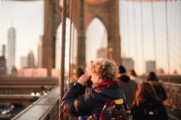teen boy taking photos of NYC on Brooklyn bridge