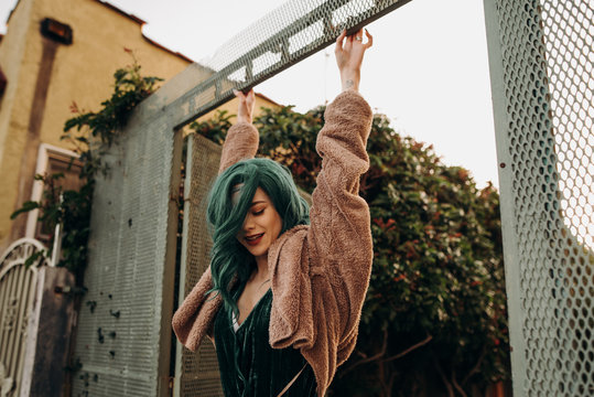 Glamorous young woman with green hair hanging off of a railing outside an apartment building