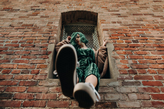 Beautiful woman with green hair sitting on a ledge of a brick wall building outside in the city