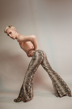 Slender crossdresser model in snake print pants