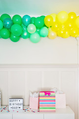 Balloon Arch over Gifts and Happy Birthday Sign