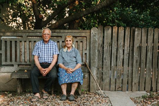 Senior man and woman on bench of farmhouse