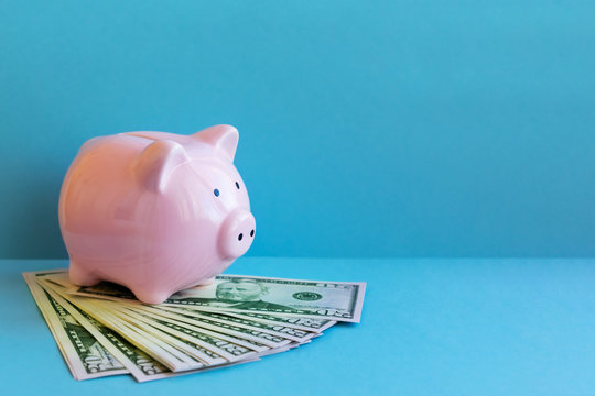 Girl is putting money into piggy bank with copy space. Concept of money saving and budgeting.
