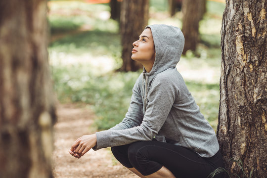A young woman resting from jogging in the park by a tree. She is wearing a grey hoodie and gazes upwards, reflecting.