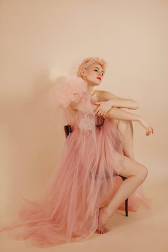 Blond woman posing at studio in pink evening gown