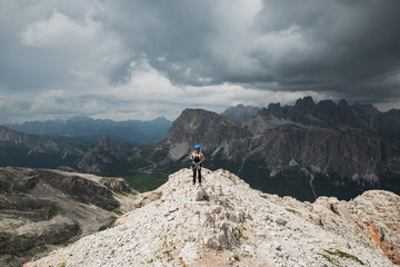 Woman climber at the top of the mountain with dark clouds in the background