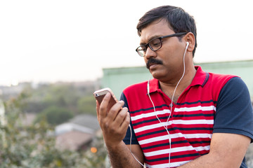 Middle aged man listening music in a smartphone with a headphone