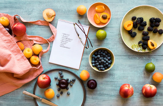 Shopping bag, shopping list and fresh fruits on blue tabletop