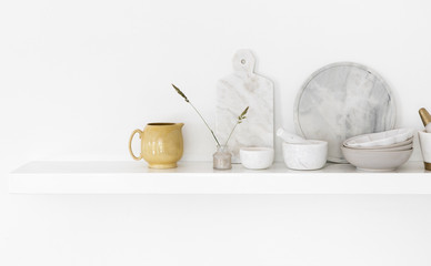 An arrangement of modern and vintage tableware on kitchen wall shelf
